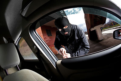 Prevent Vehicle break ins locksmith tips - Robber breaking into car